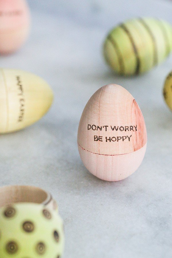 A pink Easter egg that says Don't worry be hoppy on it.
