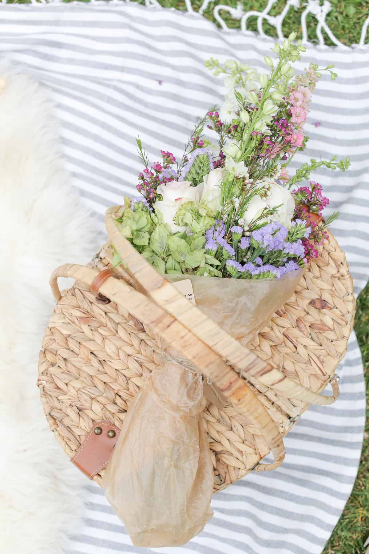 Wicker picnic basket with flowers and a picnic blanket.