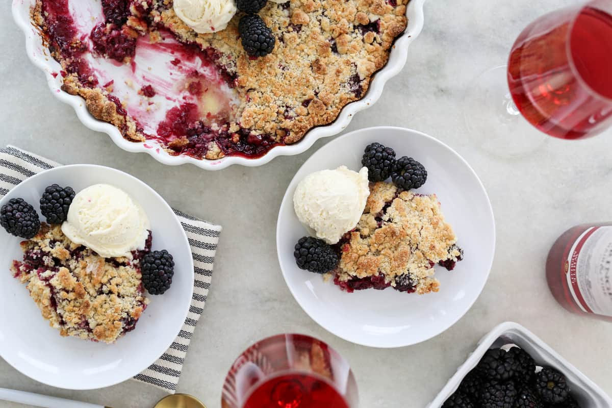 Blackberry cobbler crumble with ice cream, wine and fresh blackberries.