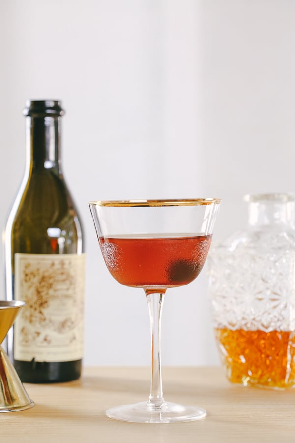 A classic Manhattan cocktail in a coupe glass with a cherry on the bottom.