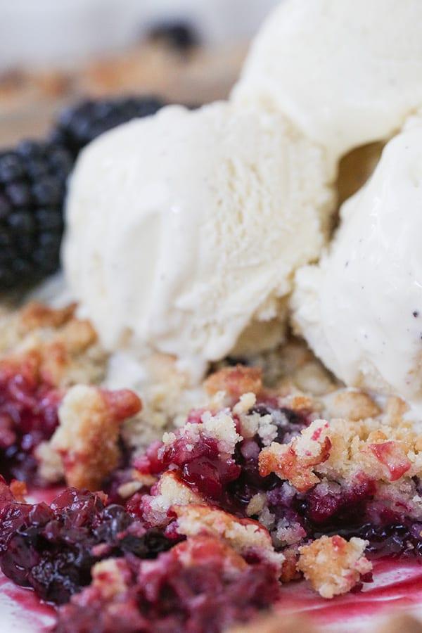 Close up of blackberry cobbler with vanilla ice cream.
