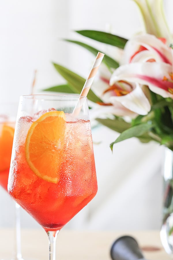 Close up photo of an Aperol Spritz with an orange slice and paper straw.