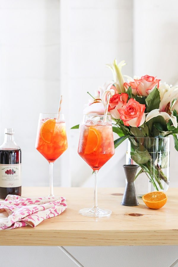 Aperol spritz with flowers, syrup and bar tools.