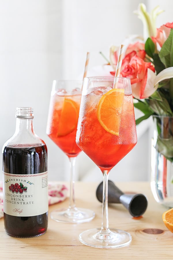 Two Aperol Spritz with Lingonberry syrup and flowers on a bar.