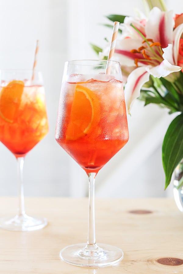 Aperol spritz with an orange slice and stripe straws.