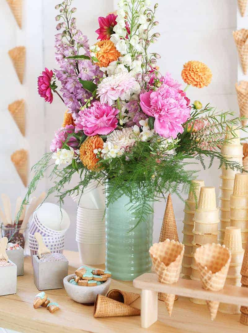 Colorful flowers in a green vase on an ice cream bar.