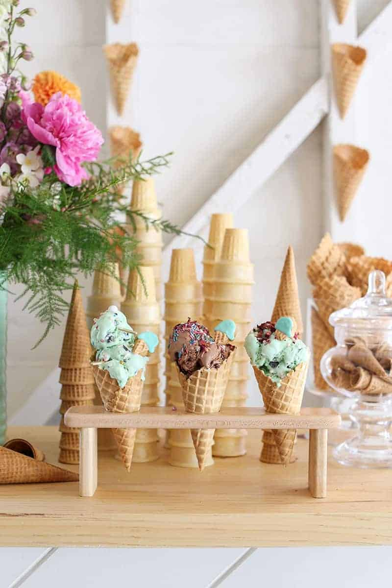 Three ice cream cones in a wooden holder on an ice cream bar.