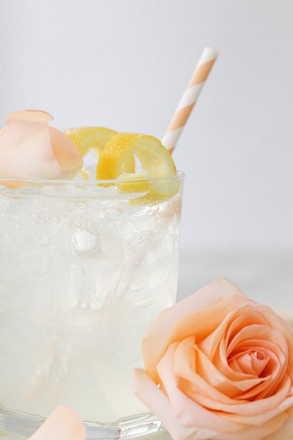 Rose water cocktail with a rose and a peach straw