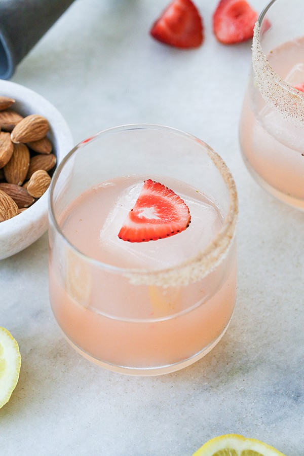 A cocktail with a slice of strawberry and large ice cube on a bar with a bowl of almonds.