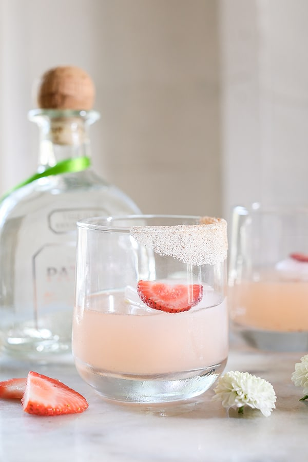 Pink cocktail with sugar rim and sliced strawberry.