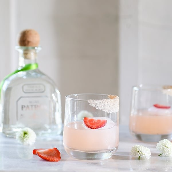 Strawberry cocktail on a bar with Patron in the back.