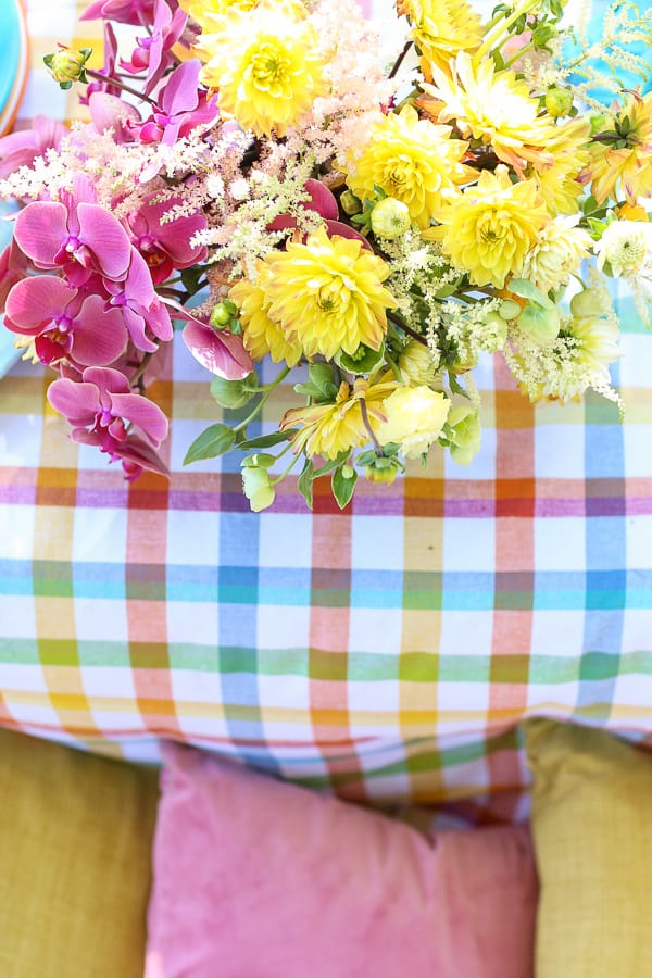 Colorful flowers, tablecloth and throw pillows.