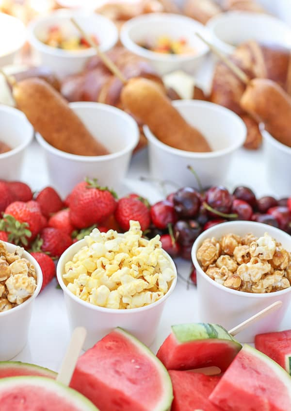 Carnival food, popcorn in cups, cherries, strawberries, corndogs,