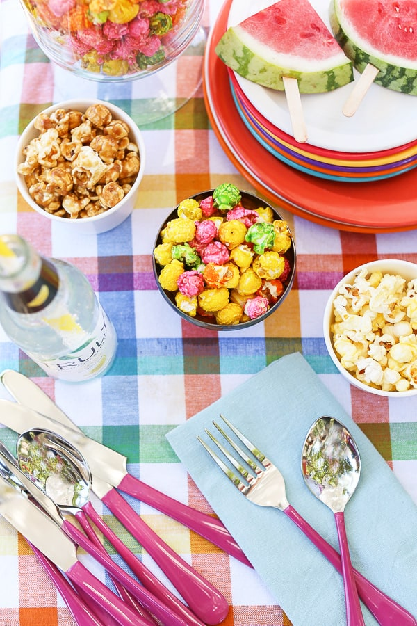 Colorful popcorn, pink flatware, napkin and colorful plates.