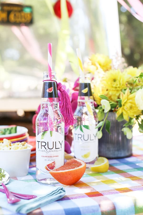 Truly spiked water, colorful flowers and fruit for a carnival party.