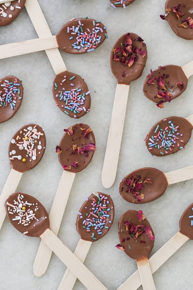 Wooden spoons dipped in chocolate with sprinkles on them.