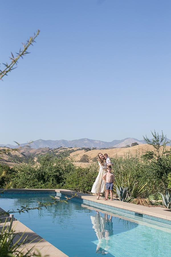 Eden Passante standing by a pool with her two boys in Los Olivos