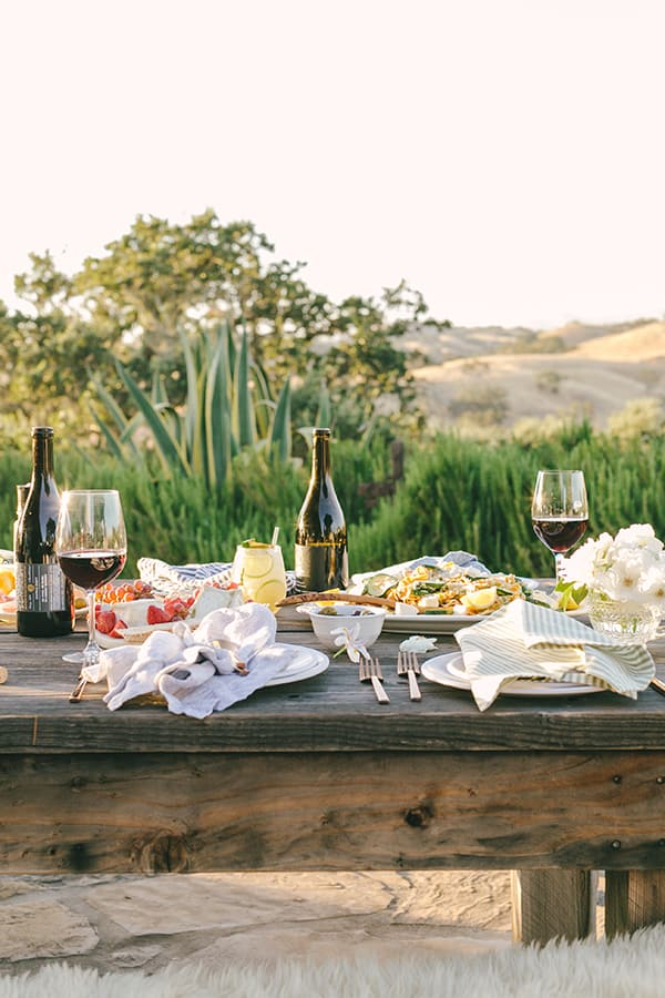 Dinner outside in Los Olivos with wine glasses and a sunny dinner.