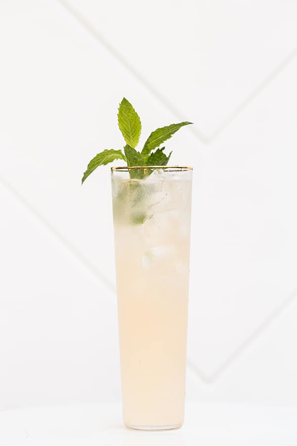 Tall clear glass with cocktail and fresh mint.