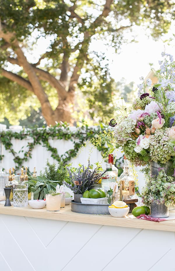 Whimsical garden cocktail bar setting with tons of flowers, herbs, limes, lemons and spirits.
