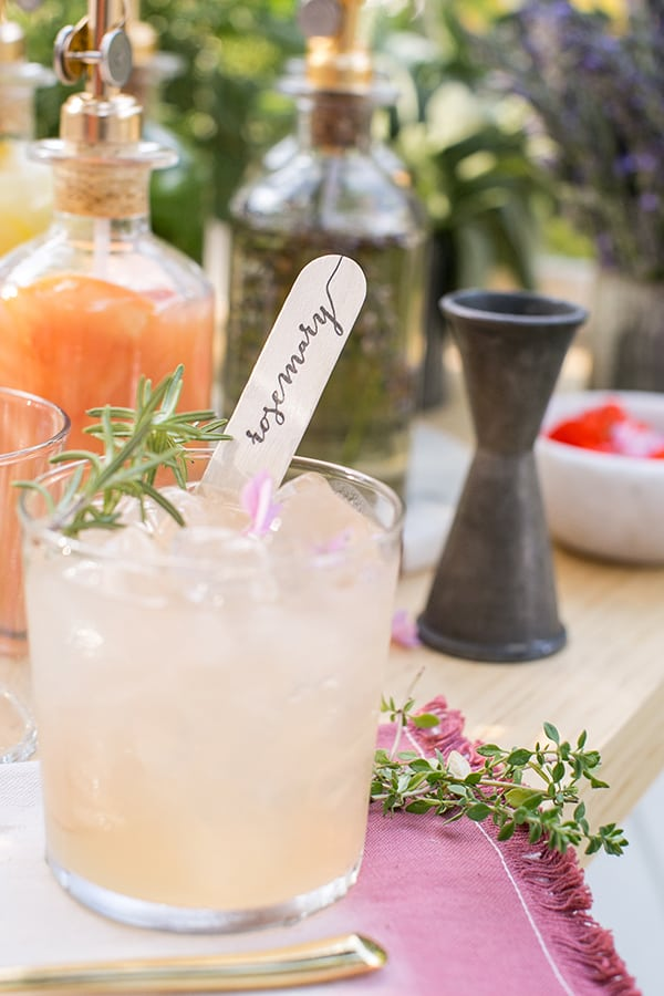 Pink cocktail with wooden stick and rosemary garnish.