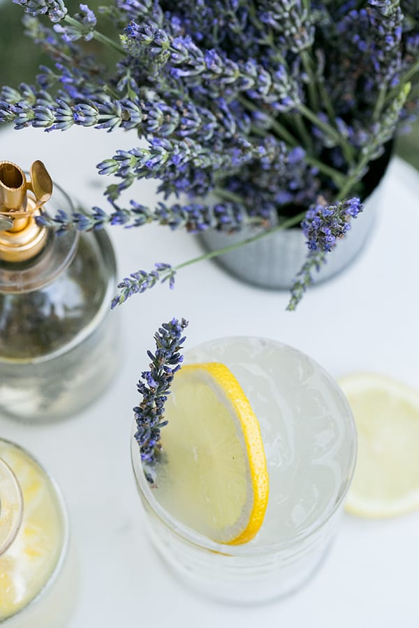 Lavender and lemon cocktail in glass with lemon garnish.