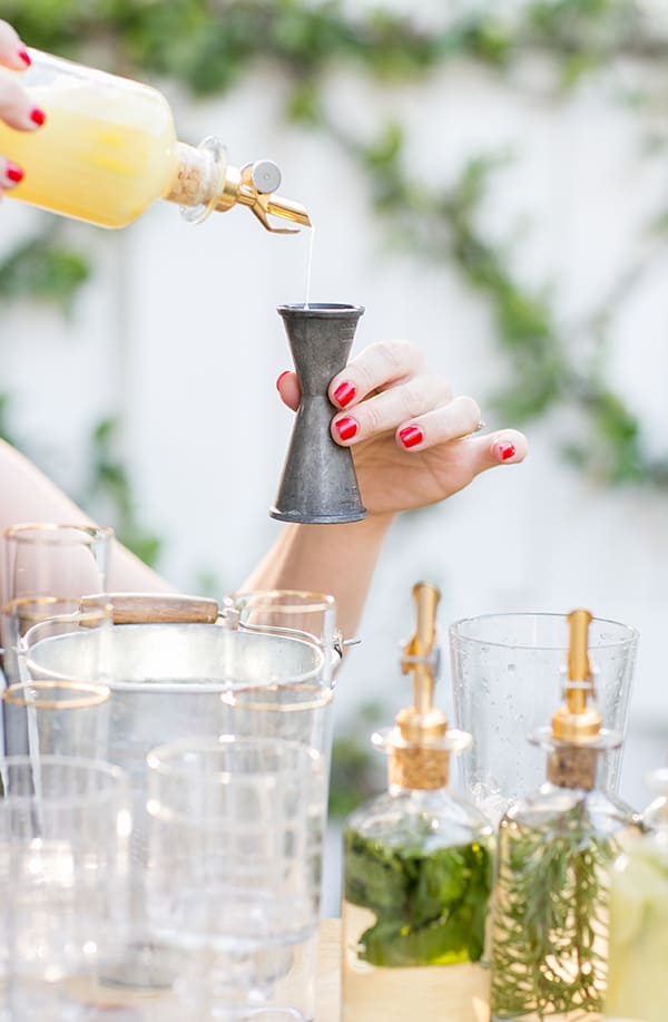 Girl pouring juice into a cocktail jigger.