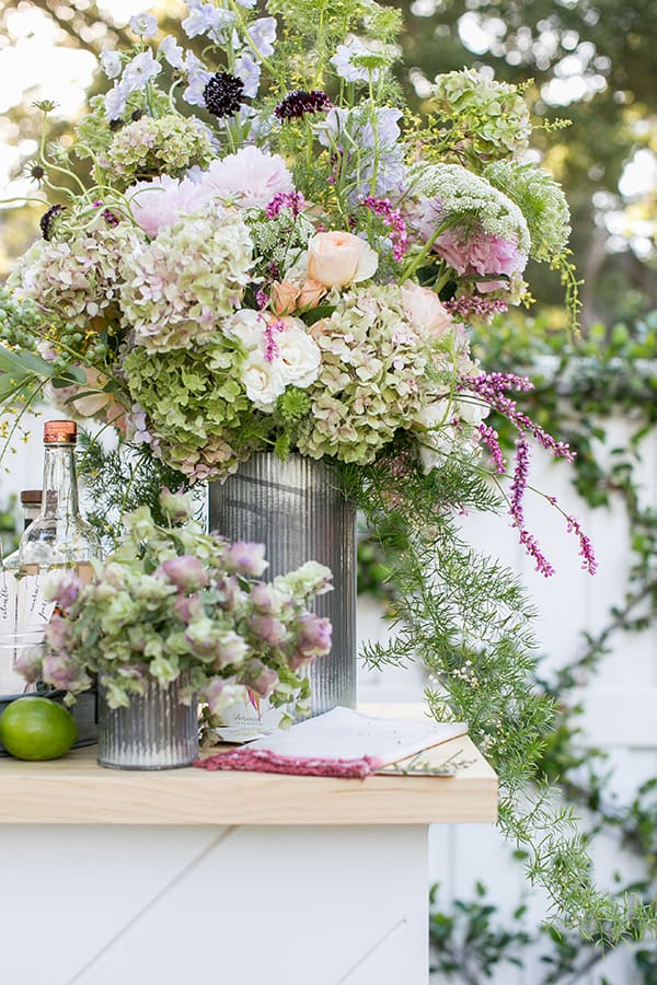 Large garden flower arrangement in a tin vase on an outdoor bar.