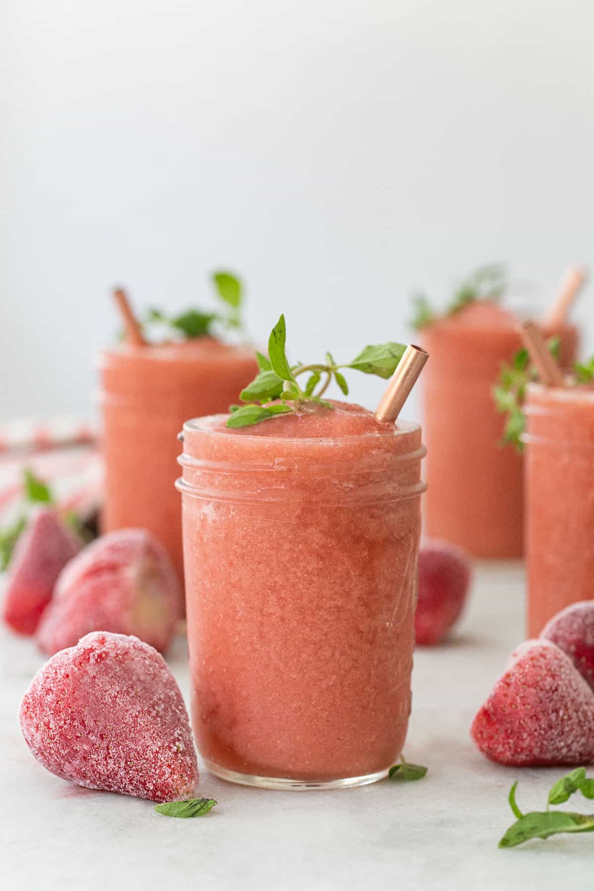 Frozé drink in a glass with frozen strawberries and a copper straw