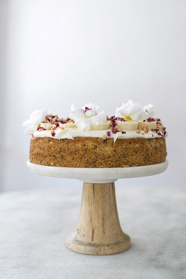 Banana cake on a cake stand topped with whipped cream cheese frosting.