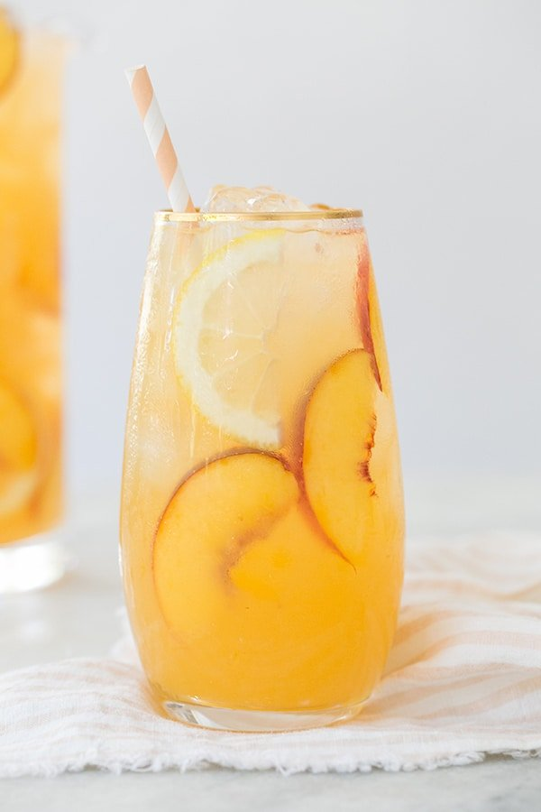Tall glass of peach lemonade with sliced peaches and lemons and a stipe paper straw.