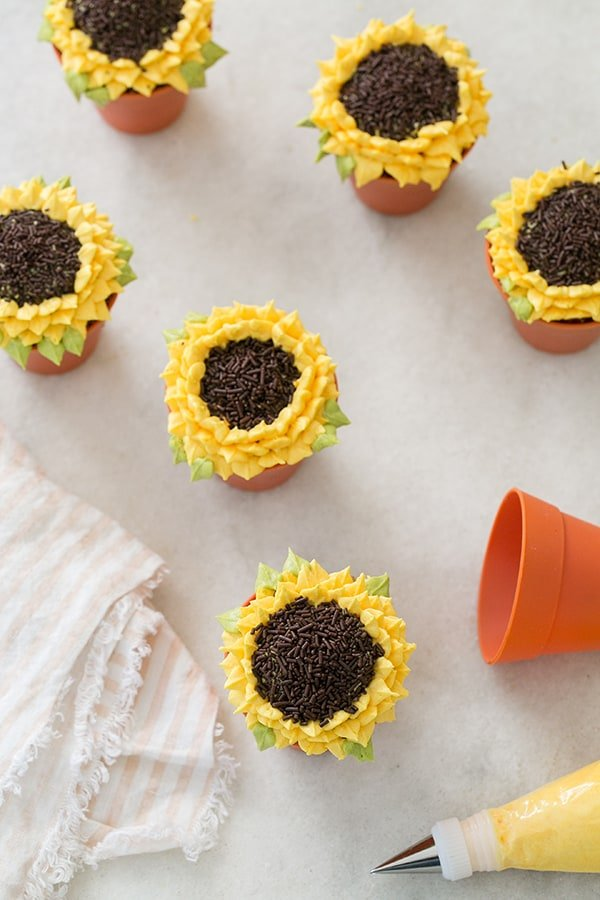 Pumpkin Spice Sunflower Cupcakes on a marble table with a piping bag and a striped pink napkin