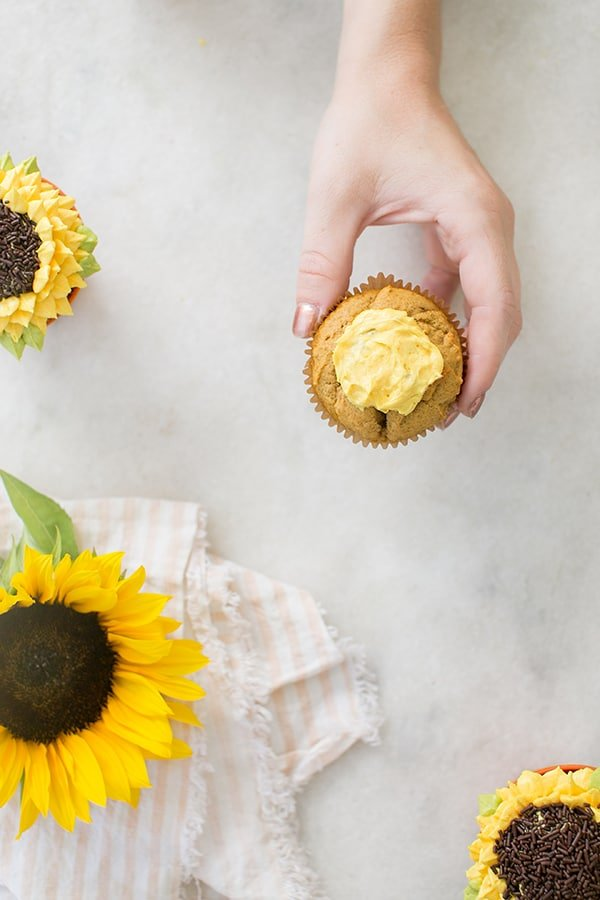 Hand holding a cupcake with a yellow frosting circle
