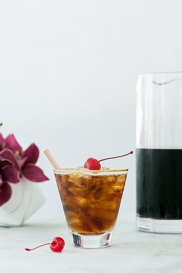 Coffee tonic recipe with a red cherry on top.