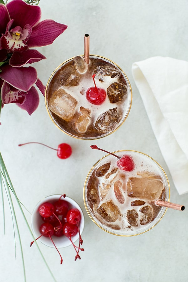 coffee tonic recipe with a cherry over the top on a marble table.
