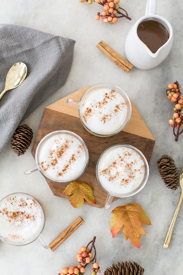 Vanilla lattes on a wooden board with falls leaves.