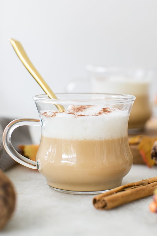 French vanilla coffee with caramel and frothy milk in a clear glass mug.
