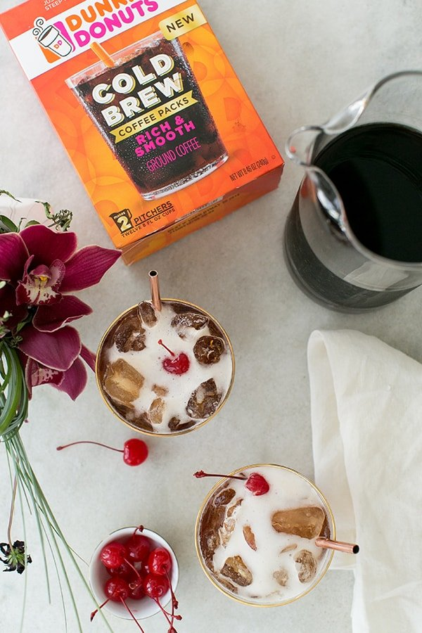coffee tonic with Dunkin' Donuts cold brew on a marble table with a bowl of cherries.