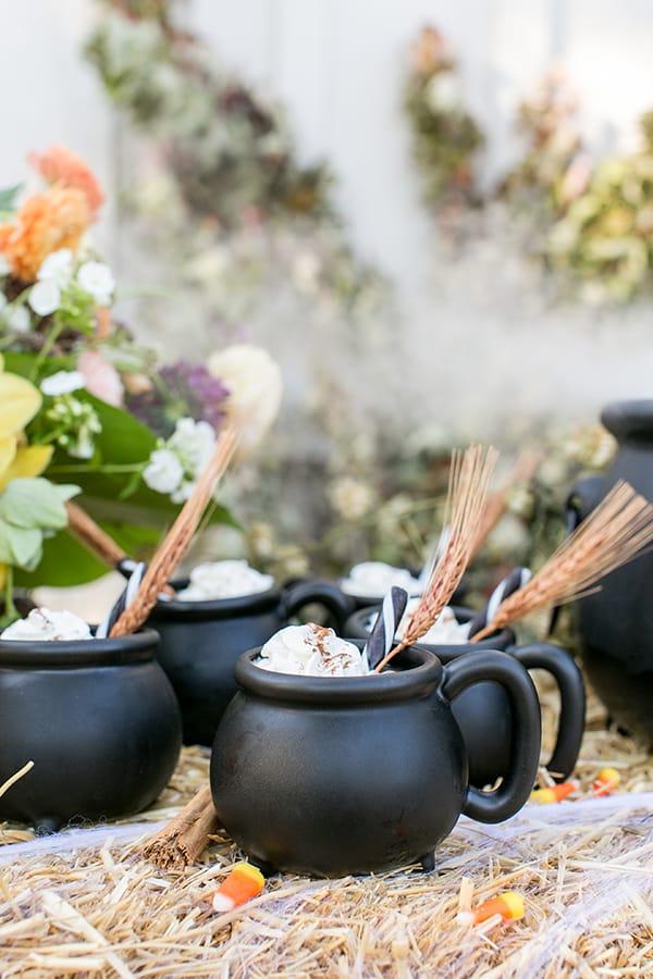side shot of 4 cauldron mugs with garnish