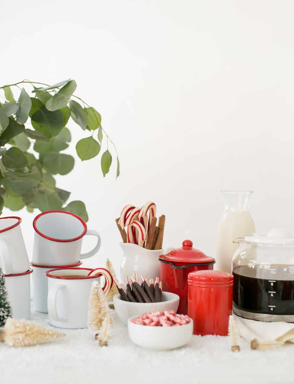 Winter coffee bar with red and white mugs, peppermint and brewed coffee.