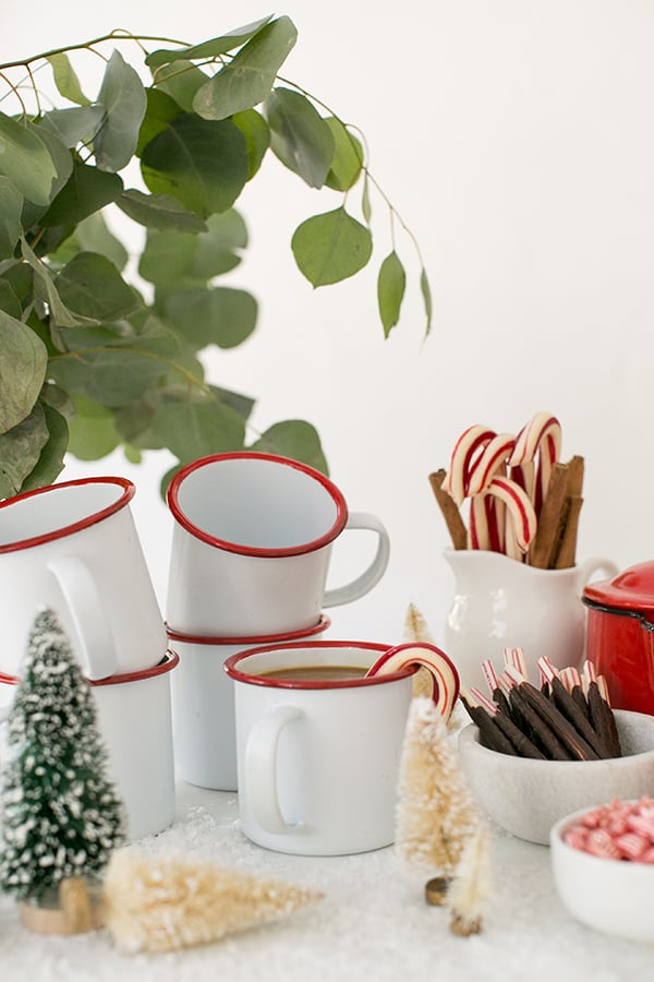 White and red enamel mugs with candy canes and mini Christmas trees for a winter coffee bar.