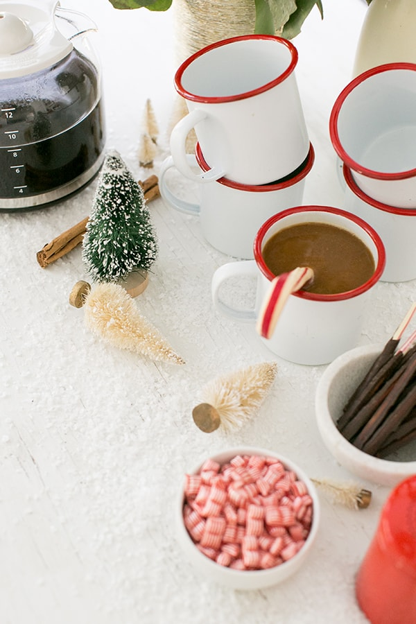 Warm coffee in red and white mugs with mini Christmas trees and peppermints.