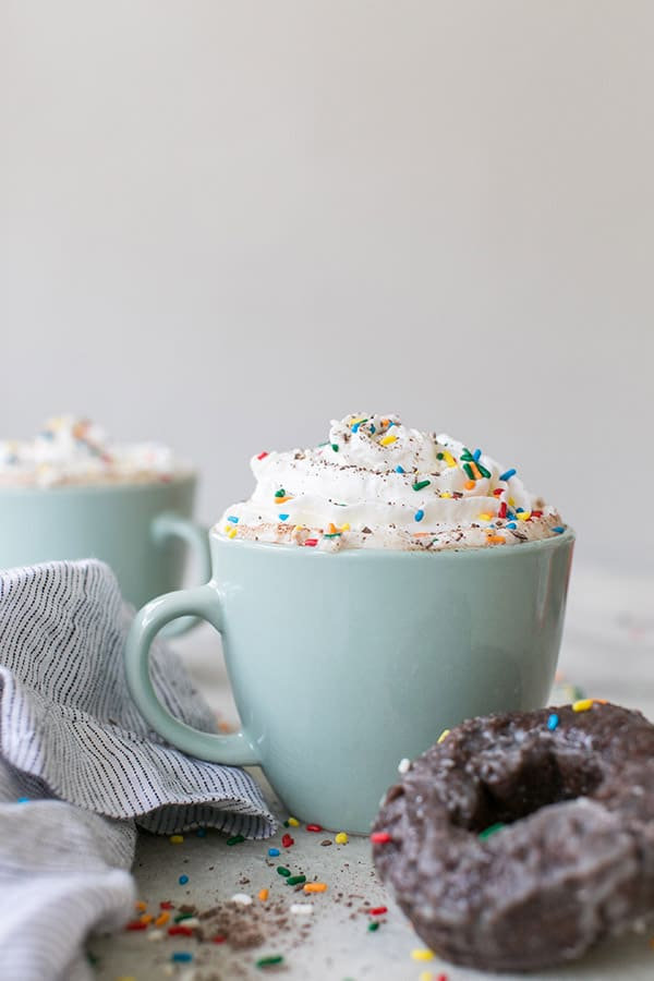 Hot chocolate coffee with whipped cream and sprinkles in a blue coffee mug.