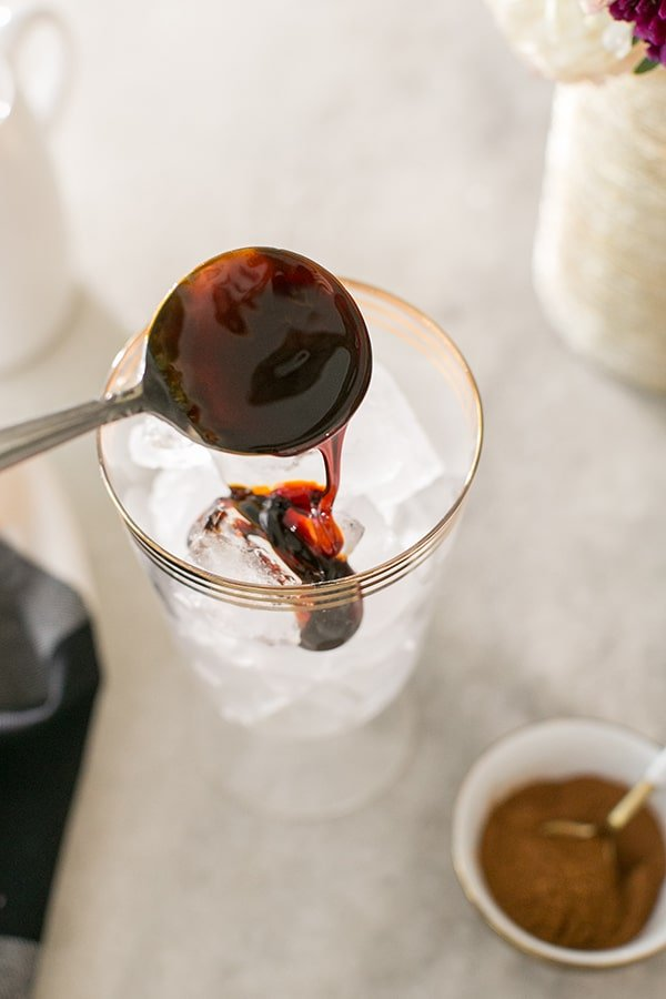 Molasses dripping in glass filled with ice.