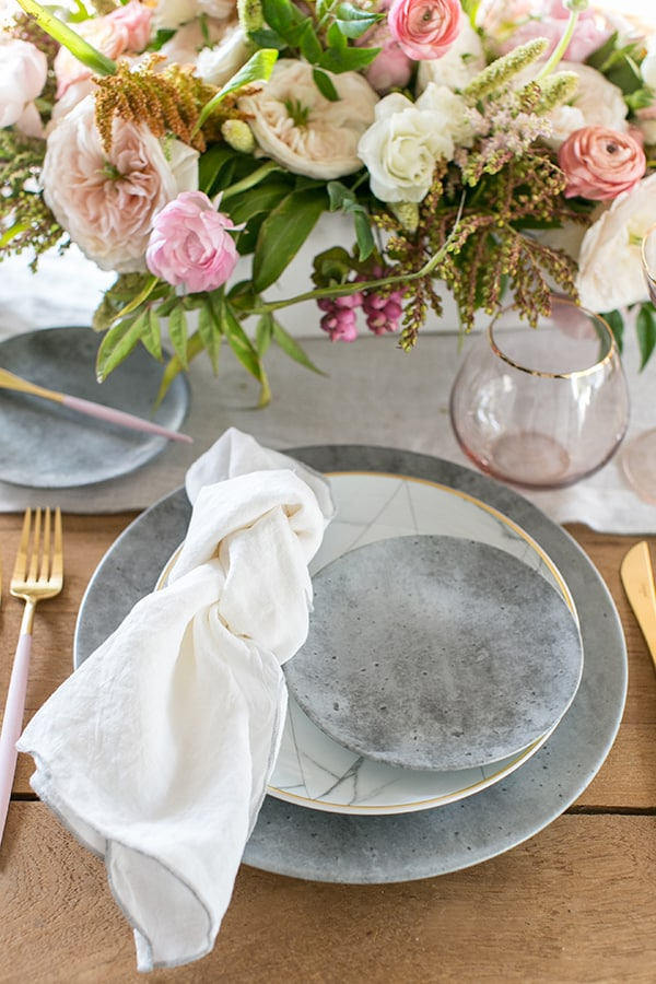 shot of flowers and a plate setting on the table