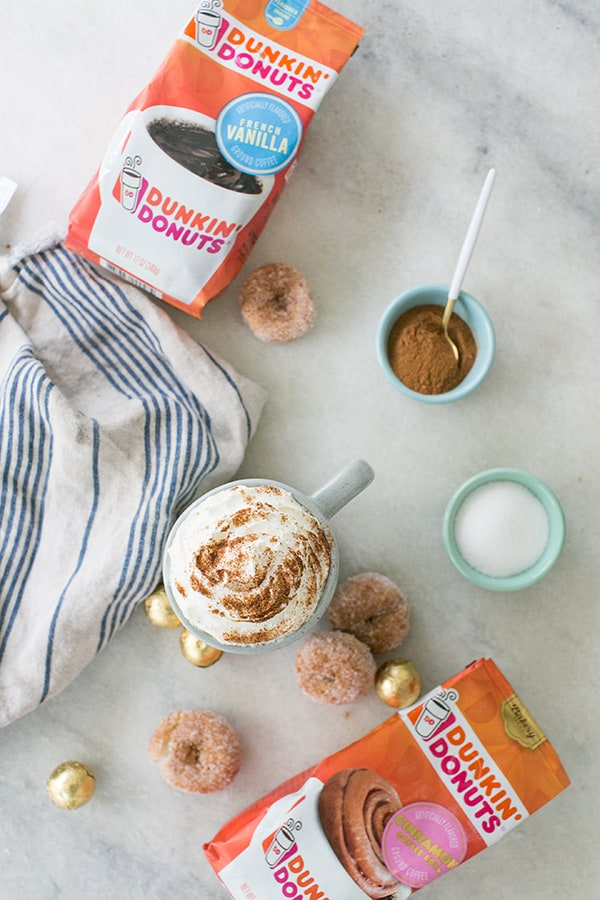 snickerdoodle coffee on a marble table with Dunkin' Donuts coffee bags and sugared doughnuts.