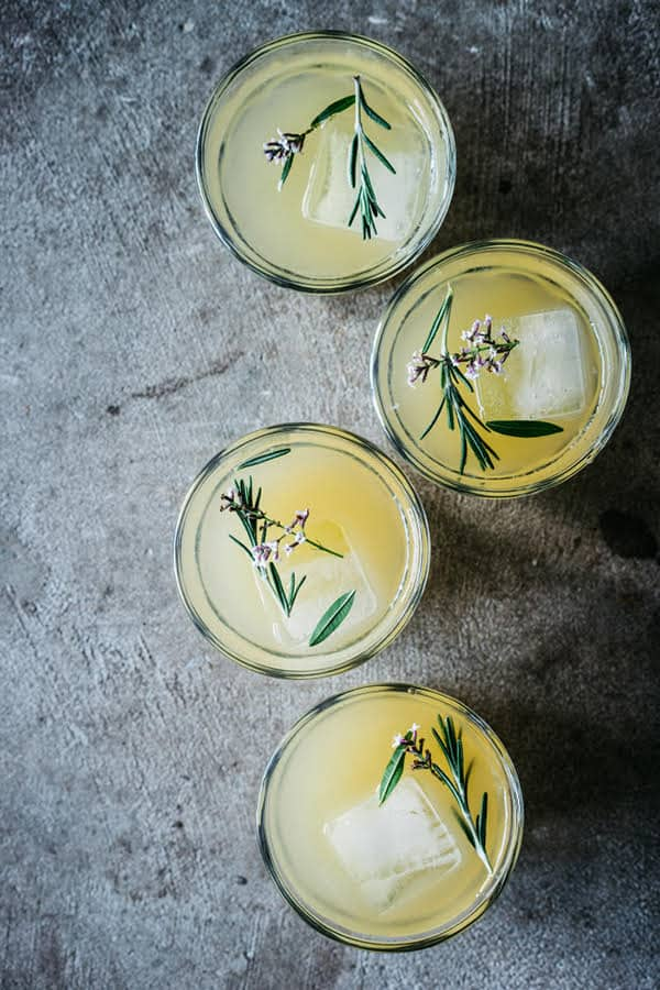 overhead picture of a pear ginger fizz with large ice cube and rosemary.