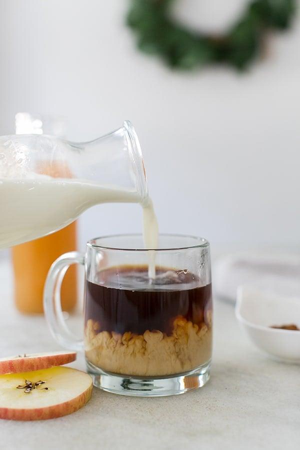 Pouring cream into black coffee.