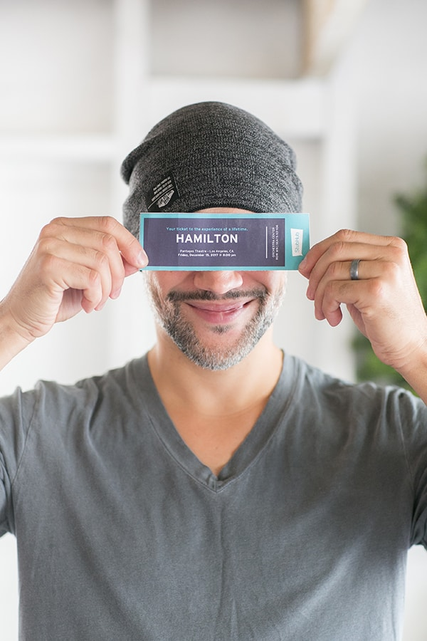 creative gift ideas - Zane holding up tickets to Hamilton