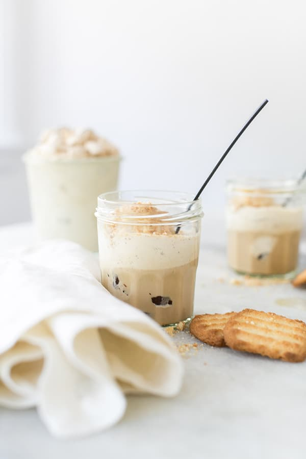 An Easy Tiramisu Coffee Dessert Recipe in a glass with a black spoon on a table.
